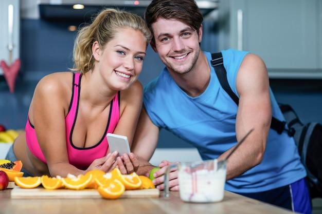 Zdrowa para patrzeje smartphone w kuchni