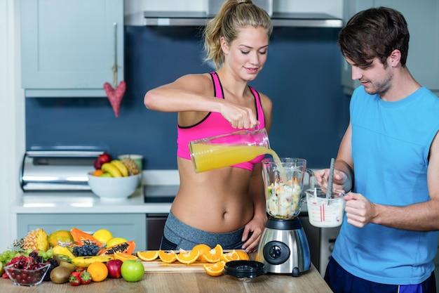 Zdrowa para przygotowuje koktajl w kuchni
