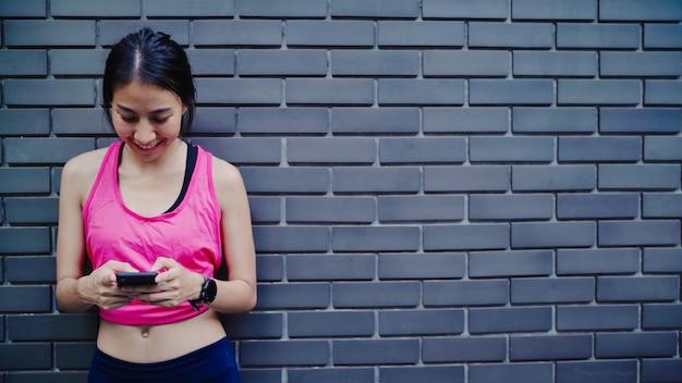 Zdrowa piękna młoda azjatycka atleta kobieta używa smartphone dla sprawdzać ogólnospołecznych środki