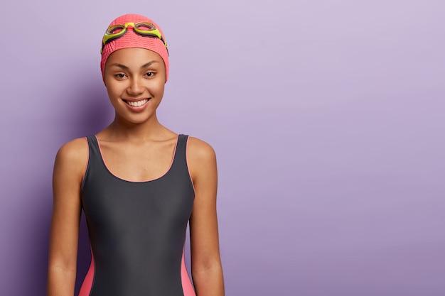 Zdrowa pływaczka nosi różową czapkę, okulary, kostium pływacki, przygotowuje się do treningu w basenie