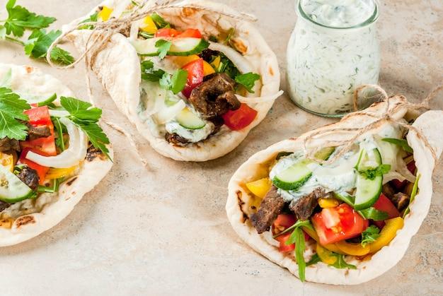 Zdrowa przekąska, lunch. tradycyjne gyros owinięte w kanapkę po grecku - tortille, chleb pita z nadzieniem warzywnym, mięsem wołowym i sosem tzatziki