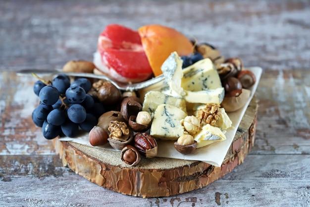 Zdrowa przekąska na drewnianej tacy. ser, orzechy i owoce. dieta ketonowa. przekąska keto.