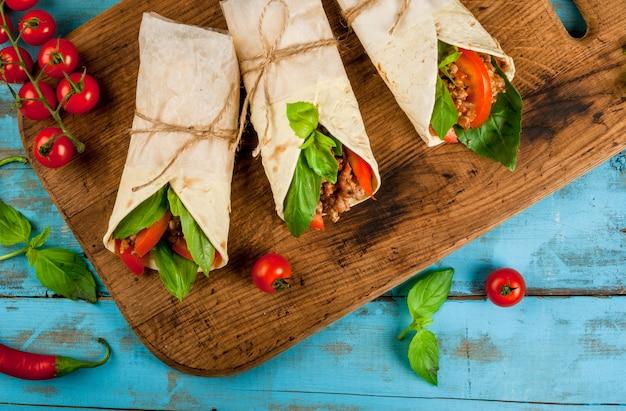 Zdrowa przekąska na lunch. kanapki przekręcająca rolki tortilla z wołowiną i warzywami drewniana tnąca deska na błękitnym drewnianym wieśniaka stole, kopii przestrzeń, odgórny widok