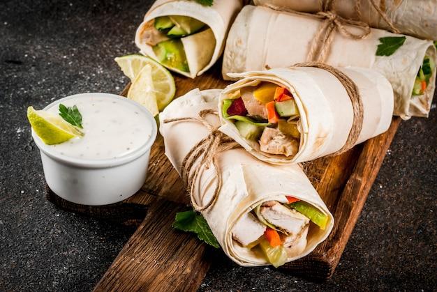 Zdrowa przekąska na lunch. stos meksykańskich ulicznych fajita z tortillą zawija się z grillowanym bawolim filetem z kurczaka i świeżymi warzywami