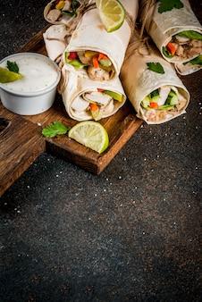 Zdrowa przekąska na lunch. stos meksykańskiej żywności fajita z tortillą zawija się z grillowanym filetem z bawolego kurczaka