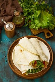 Zdrowa przekąska na lunch tortilla wrapy z grillowanym kurczakiem i świeżymi warzywami chicken tortilla