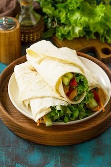 Zdrowa przekąska na lunch tortilla wrapy z grillowanym kurczakiem i świeżymi warzywami na niebieskim stole