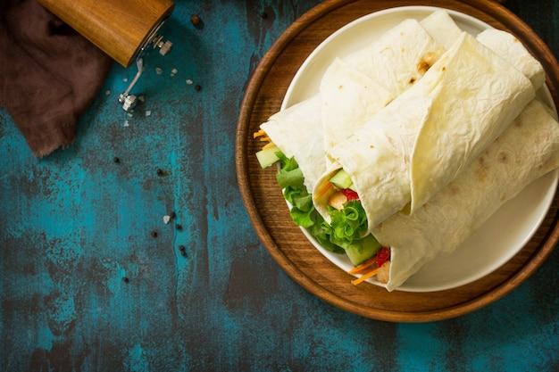 Zdrowa przekąska na lunch tortilla wrapy z grillowanym kurczakiem i świeżymi warzywami