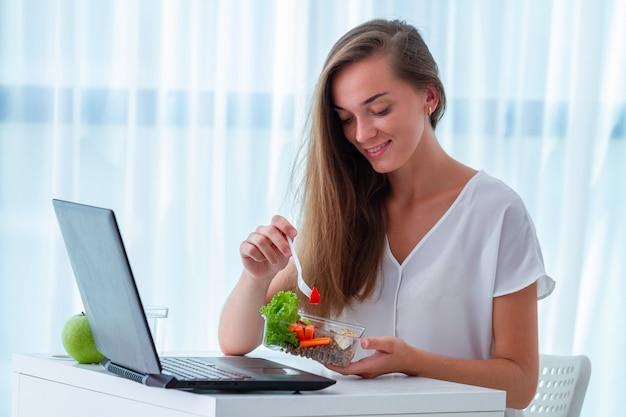 Zdrowa przekąska w biurze. szczęśliwa biznesowa kobieta je posiłki od lunchu pudełka przy pracującym stołem podczas lunchu czasu