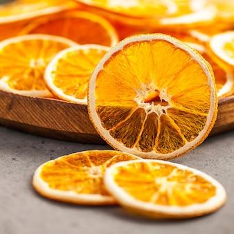 Zdrowa przekąska. wysuszony pomarańcze pokrajać zakończenie na drewnianym talerzu.