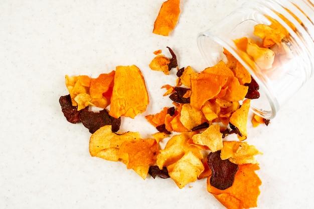 Zdrowa przekąska z chipsów warzywnych z buraków, marchwi, pasternaku na jasnym tle
