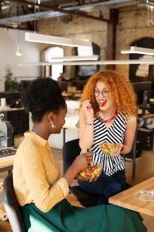 Zdrowa pyszna sałatka. dwóch modnych projektantów jedzących zdrową pyszną sałatkę podczas przerwy w pracy