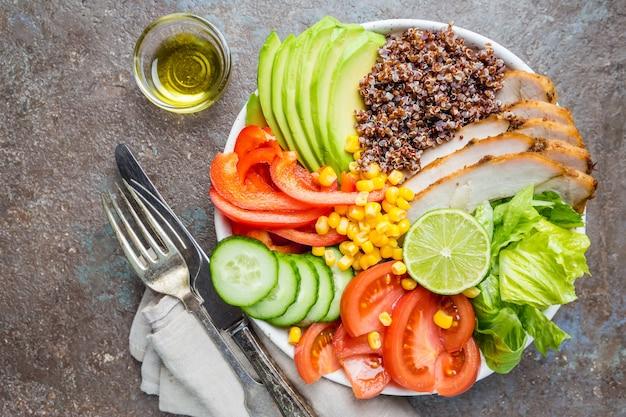 Zdrowa salaterka z komosą ryżową, pomidorem indykiem, awokado, słodką papryką, kukurydzą, limonką i mieszanymi warzywami, widok z góry. poczęcie zdrowej żywności. posiłek superfood.