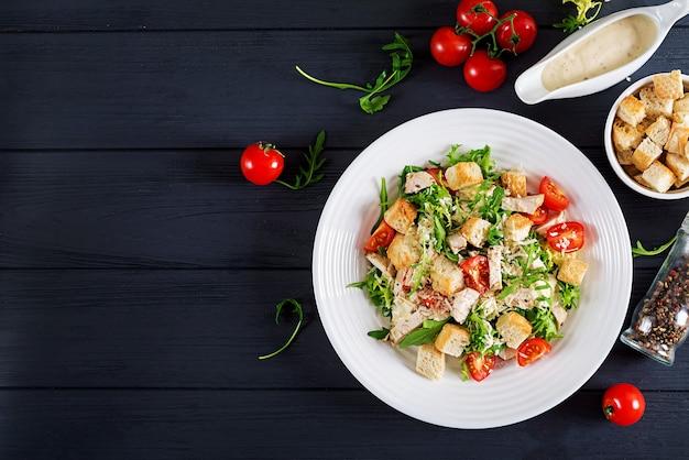 Zdrowa sałatka cezar z kurczaka z grilla z pomidorami, serem i grzankami.