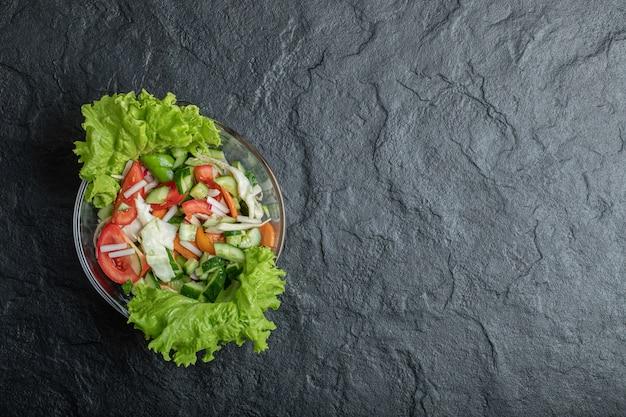 Zdrowa sałatka jarzynowa ze świeżych pomidorów, ogórka, cebuli na talerzu. wysokiej jakości zdjęcie