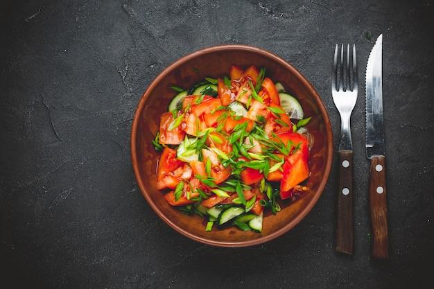Zdrowa sałatka jarzynowa ze świeżych pomidorów, ogórków, cebuli, szpinaku, sałaty