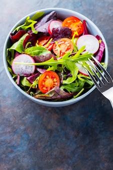 Zdrowa sałatka, liście mix sałat. sałatka wegańska z pomidorkami koktajlowymi, rzodkiewką i mixem sałat. koncepcja diety keto lub paleo. skopiuj miejsce. widok z góry