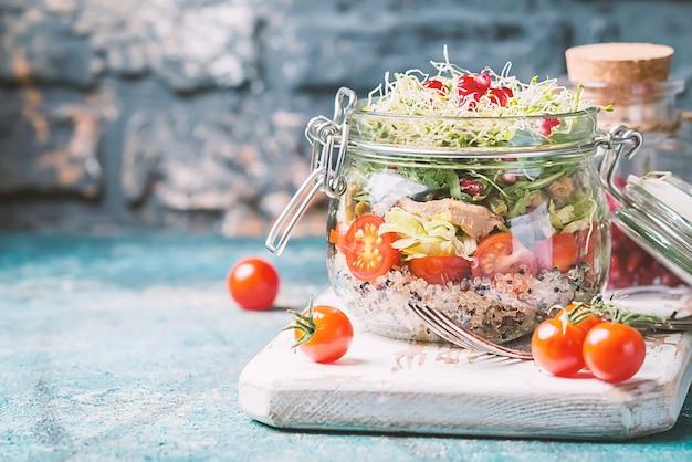 Zdrowa sałatka w szklanym słoju z komosą ryżową, warzywami i zielenią - koncepcja zdrowej żywności lub diety