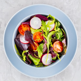 Zdrowa sałatka warzywna z pomidorkami koktajlowymi, rzodkiewką i mixem sałat. sałatka wegańska z mieszanką zieleni na szarym tle. koncepcja diety paleo. skopiuj miejsce. widok z góry