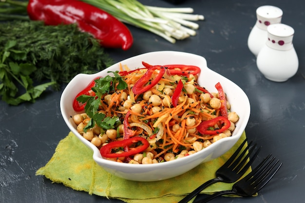 Zdrowa sałatka z ciecierzycy, koreańskiej marchewki, słodkiej papryki i cebuli ozdobiona czarnym sezamem