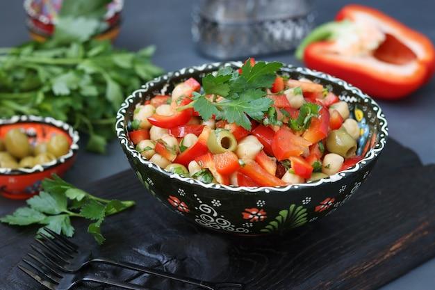 Zdrowa sałatka z ciecierzycy, zielonych oliwek, pieprzu i pietruszki na desce na czarno