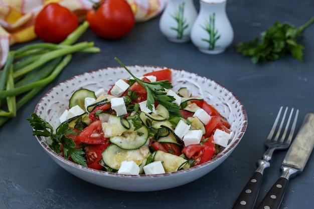 Zdrowa sałatka z cukinii, pomidorów i fety, ubrana z oliwą z oliwek w talerzu na ciemnej powierzchni, w orientacji poziomej