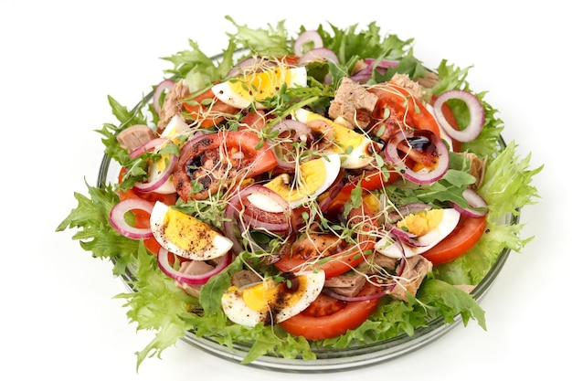 Zdrowa sałatka z ekologicznej sałatki z tuńczykiem w puszce, pomidorami, jajami, rukolą, czerwoną cebulą i mikrogranulą w talerzu na białej powierzchni