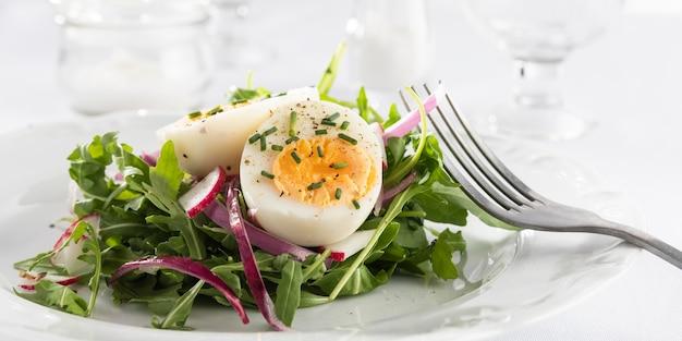 Zdrowa sałatka z jajkiem na białym talerzu