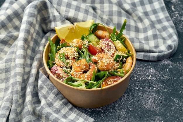 Zdrowa sałatka z krewetkami, rukolą, ogórkiem, pomidorkami koktajlowymi i sosem w opakowaniu dostawczym na ciemnej powierzchni. ścieśniać