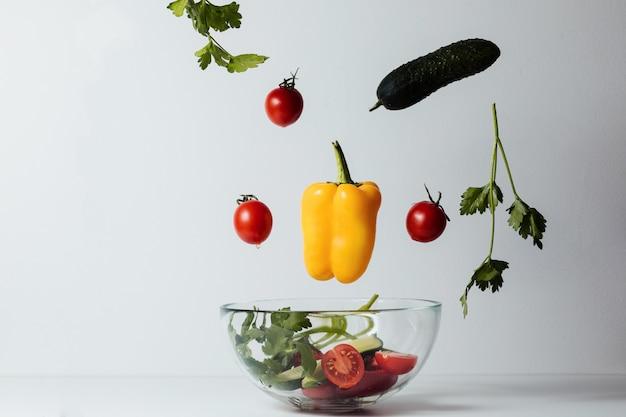 Zdrowa sałatka z latającymi jarzynowymi składnikami na bielu
