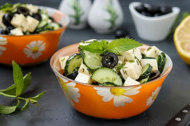 Zdrowa sałatka z ogórkami, fetą i oliwkami, z oliwą z oliwek i zieleniną, w miskach na tle ciemnego, poziomego zdjęcia