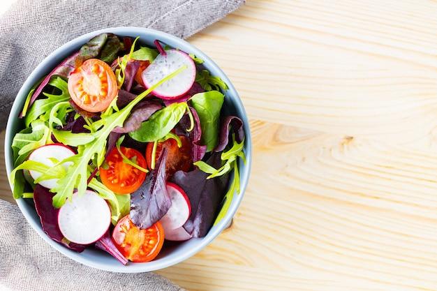 Zdrowa sałatka z pomidorkami koktajlowymi, rzodkiewką i mixem sałat. sałatka z mieszanką zieleni na drewnianym tle. skopiuj miejsce