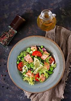 Zdrowa sałatka z rybami. pieczony łosoś, pomidory, limonka i sałata. zdrowy obiad leżał płasko. widok z góry
