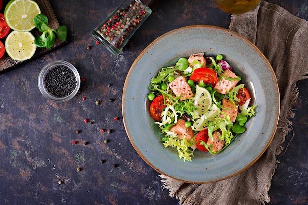 Zdrowa sałatka z rybami. pieczony łosoś, pomidory, limonka i sałata. zdrowy obiad leżał płasko.