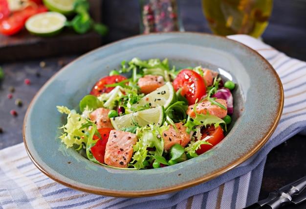 Zdrowa sałatka z rybami. pieczony łosoś, pomidory, limonka i sałata. zdrowy obiad