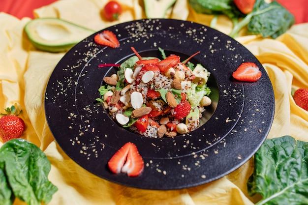 Zdrowa sałatka z truskawkami na talerzu