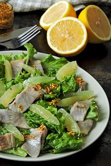 Zdrowa sałatka z zielonymi liśćmi, śledziem i cytryną. sałatka śledziowa z cytryną. dieta ketonowa. zdrowy obiad lub kolacja.