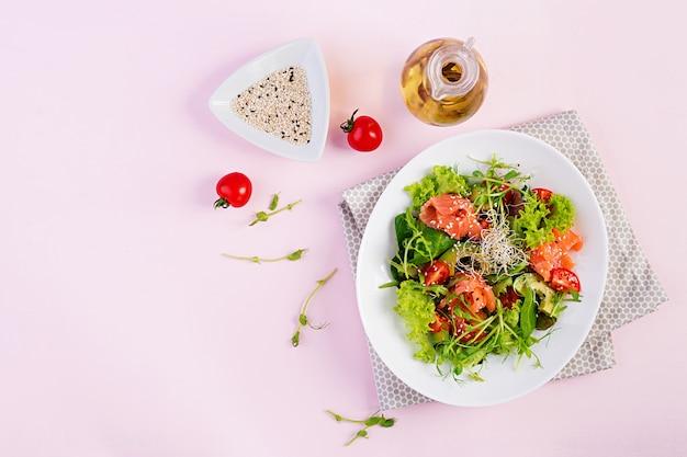 Zdrowa sałatka ze świeżych warzyw, pomidorów, awokado, rukoli, nasion i łososia