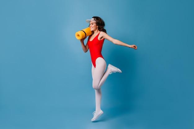 Zdrowa silna młoda kobieta lat 80-tych uprawia sport na niebieskiej ścianie