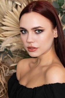 Zdrowa skóra włosy ciało kobiety naturalne piękno czystej skóry tworzą długie włosy brunetka modelki, brunetka dziewczyna z bordowymi ustami na tle wiosennych kwiatów polnych suchych. otwarte ramiona