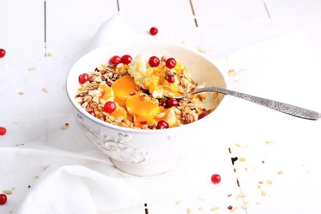 Zdrowa śniadaniowa owsianka ryżowa z puree z mango, bananem i granola