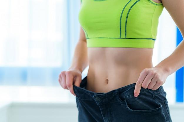 Zdrowa sport fitness szczupła kobieta wyciągając duże dżinsy i pokazując wyniki odchudzania i diety. motywacja i postęp w odchudzaniu