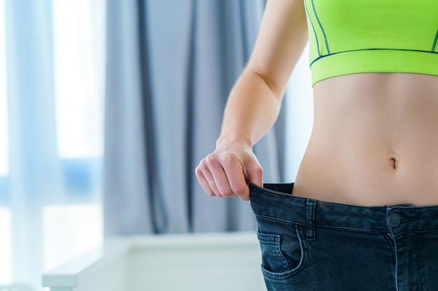 Zdrowa sport fitness szczupła kobieta wyciągając jej duże dżinsy i pokazano wyniki odchudzania i diety. postęp w odchudzaniu