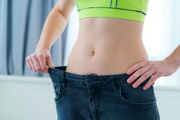 Zdrowa sport fitness szczupła kobieta wyciągając jej duże dżinsy i pokazano wyniki odchudzania. osiągnięcie celu, motywacja i postęp w odchudzaniu