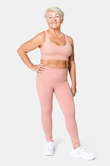 Zdrowa starsza kobieta w różowym sportowym staniku i legginsach na całe ciało