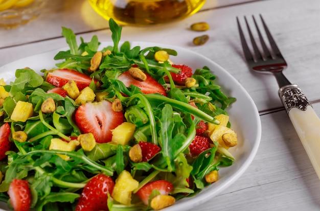 Zdrowa świeża sałatka z rukolą, truskawkami, ananasem i pistacjami serwowana na białym talerzu na rustykalnym drewnianym stole.