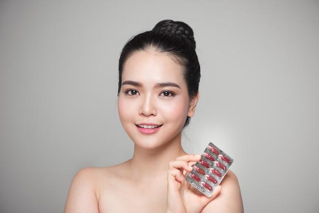 Zdrowa szczęśliwa azjatykcia kobieta z pigułkami w ręku.