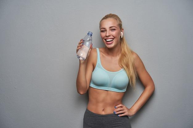 Zdrowa, urocza, długowłosa blondynka ubrana w sportowe ubrania, pozując na jasnoszarym tle, pijąc wodę źródlaną po siłowni i uśmiechając się radośnie do kamery