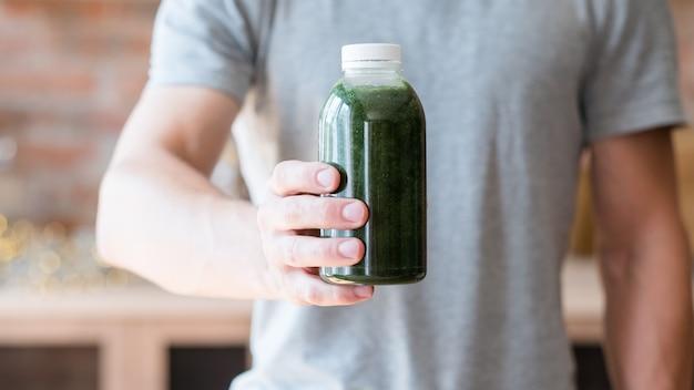 Zdrowa utrata wagi. zbilansowana dieta detoksykacyjna. wegetariański styl życia. mężczyzna oferuje butelkę świeżego zielonego smoothie.