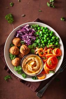 Zdrowa wegańska miska na lunch z falafelowym hummusem, marchewką, kapustą, kapustą i groszkiem